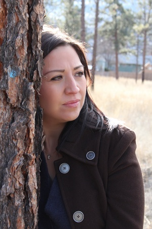 Beautiful brunette female leaning against a tree looking out photo