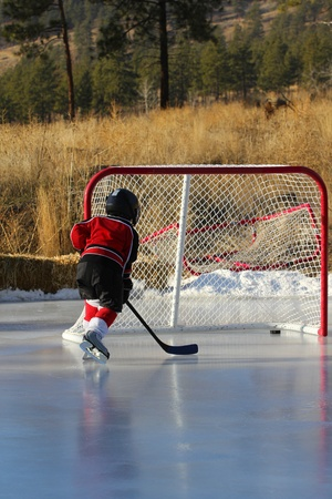 Child hockey player playing outdoor pond hockey