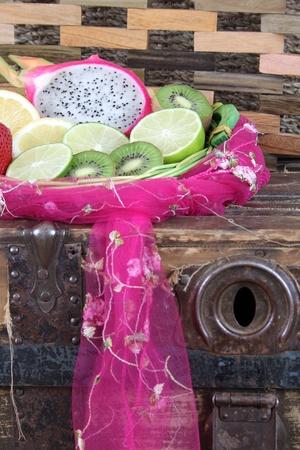 Fruit basket on an antique trunk with pink fabric photo