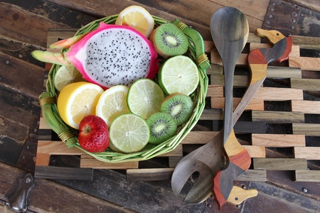 Fruit basket on wooden placemat with ornate spoons photo