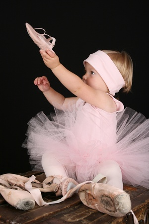 Blond toddler wearing a tutu holding Ballet shoes