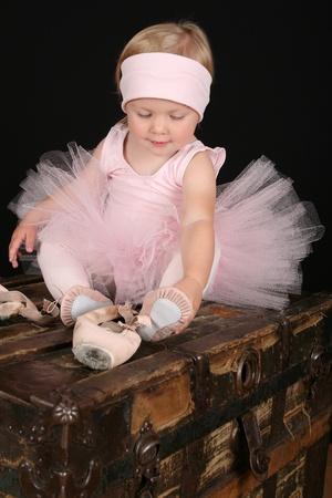 Blond toddler wearing a tutu holding Ballet shoes