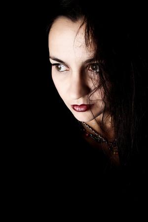 Dramatic brunette female against black background wearing black photo