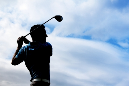 Young golfer driving with a wood against cloudy skies Stock Photo