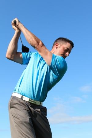 golfing: Jonge golfer het rijden met een hout tegen wolkenluchten