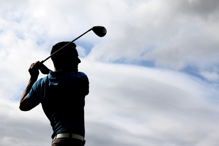 Young golfer driving with a wood against cloudy skies Archivio Fotografico