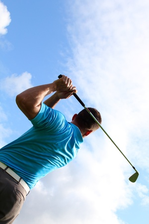 Young golfer hitting a shot with an iron