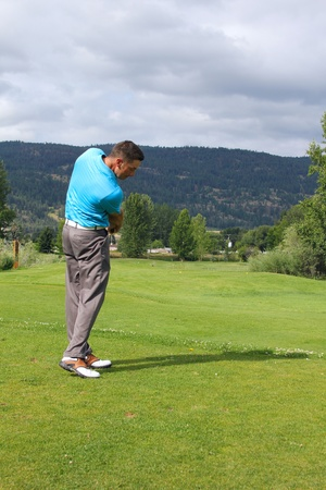 Young golfer hitting a shot with an iron Stock Photo - 10181457