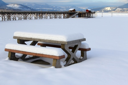 Snow covered picnic bench at Salmon Arm Pier, BC, CANADA photo