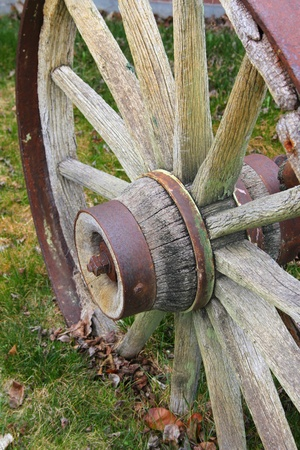 Rustic worn wooden wagon wheel on grass photo