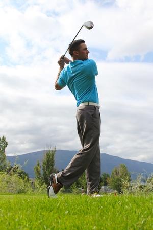 columpios: Joven golfista conduciendo con una madera contra cielos nubosos