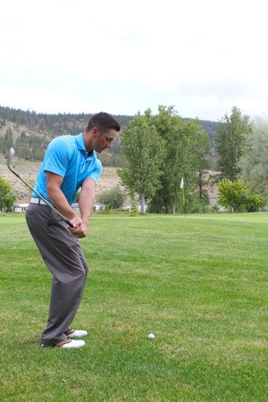 Young golfer hitting a fairway shot with an iron photo