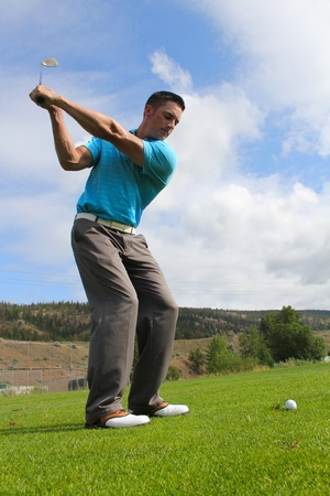 professional sport: Young golfer hitting a fairway shot with an iron