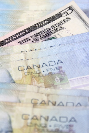 canadian cash: Five dollar Canadian bills with an American bill inbetween