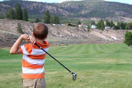 golfing: Jonge golfer het afspelen van een schot vanaf de tee box Stockfoto