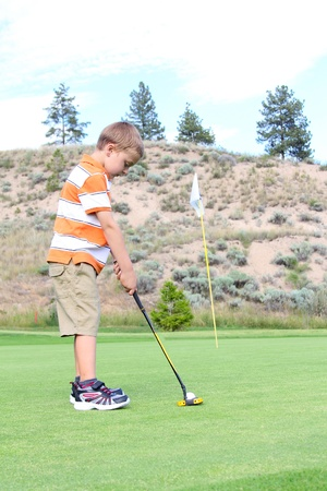 Young golfer putting his ball on the green photo