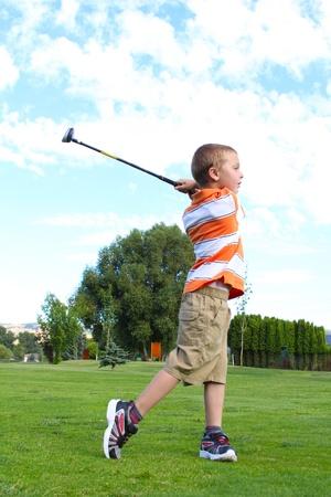 golfing: Jonge golfer het afspelen van een schot vanaf de fairway Stockfoto