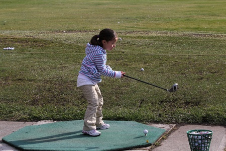 driving range: Young female golfer practising on the driving range Stock Photo