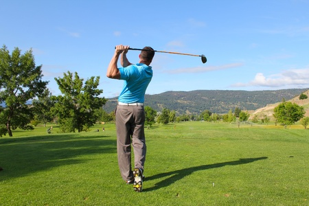 golf equipment: Young male golfer hitting a driver from the tee-box Stock Photo
