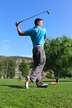 Young male golfer following a shot from the tee