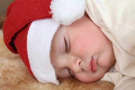 Baby boy wearing a christmas hat sleeping sound photo