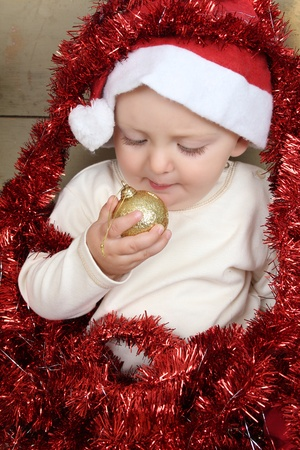 Cute baby boy wearing a christmas hat playing with decorations photo