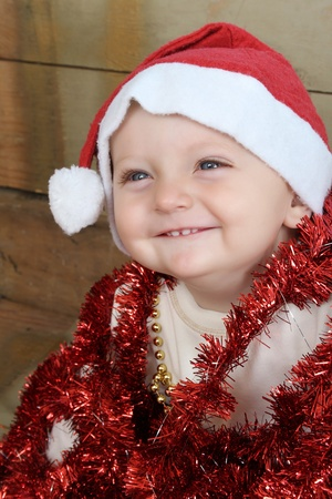 Christmas baby playing with decorations wearing a hat photo