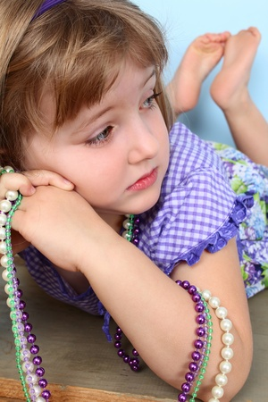 Cutle little girl lying, resting her cheek on her hands