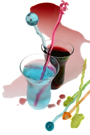 Red wine spill and a blue spirit in small glass photo