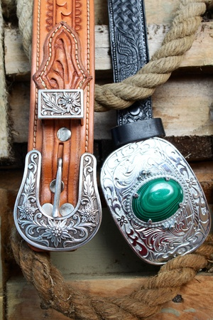 Two leather belts with silver buckles against old ammunition cases Archivio Fotografico
