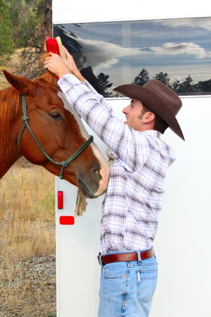 Young cowboy grooming his horse at the trailor Stock Photo - 11279535