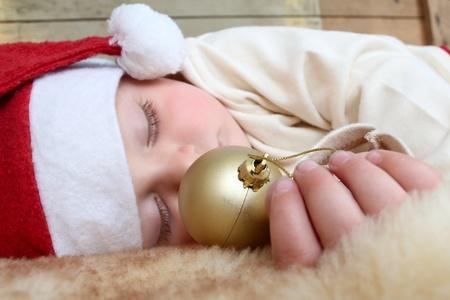 Beautiful sleeping christmas baby boy on soft rug photo