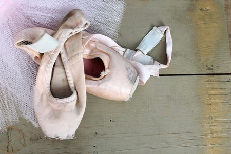 Worn pointe shoes on a pink net tutu