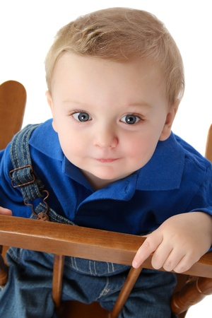 Cute baby boy sitting on a chair looking up photo