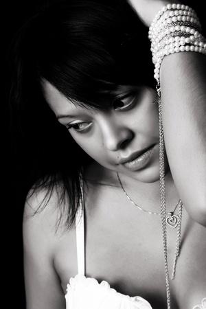 Beautiful brunette female in lingerie against black photo