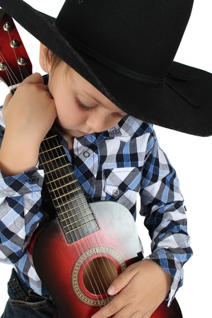 Beautiful blond cowboy wearing a hat holding guitar photo