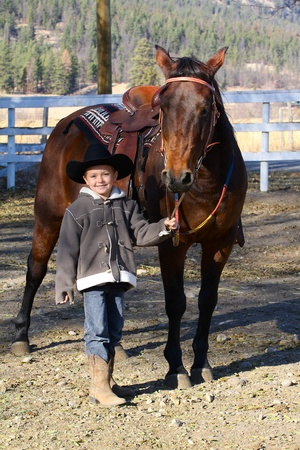 Young boy wearing a cowboy hat with his horse photo
