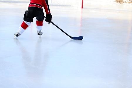 hockey sobre cesped: Ni�o peque�o jugando hockey sobre hielo en un estanque Foto de archivo