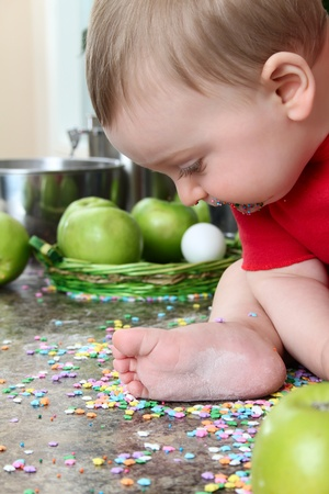 Cute baby boy looking down at candy stars on kitchen counter photo