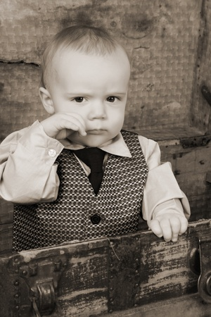 Baby boy playing inside an antique trunk photo