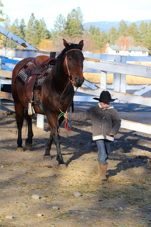Young boy leading his horse in the riding pen photo