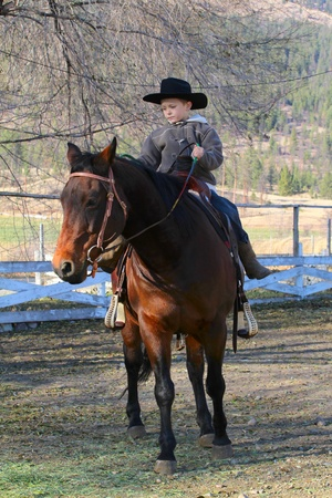 Young cowboy with hat riding his horse photo