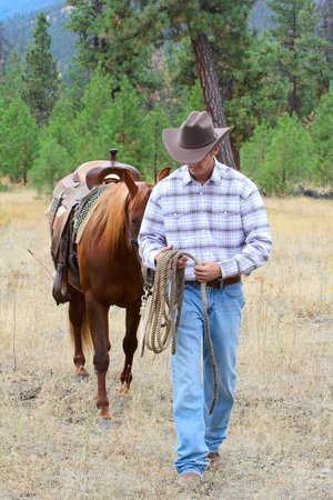 cowboy man: Young cowboy leading his horse through the field Stock Photo