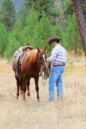 Young cowboy busy with his horse in the field photo