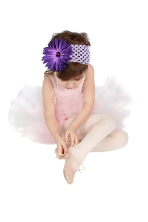 Little ballet girl putting on her shoes photo