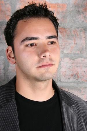 Male model against a rough brick wall background  Reklamní fotografie