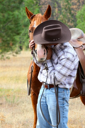 western saddle: Cowboy with his horse in the field