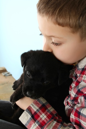 blind child: Beautiful blond boy with a black puppy Stock Photo