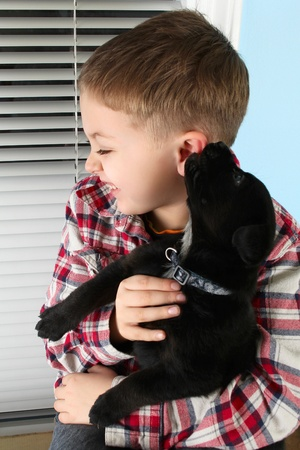 Beautiful blond boy with a black puppy photo