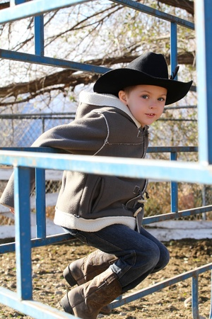 Young cowboy wearing a hat and fleece jacket  photo